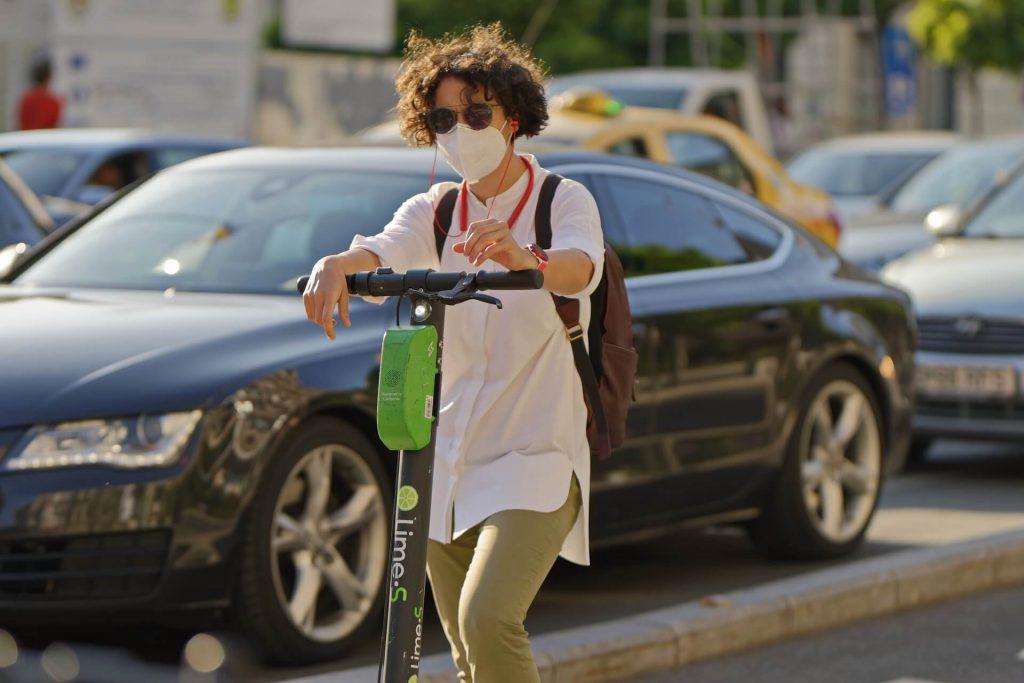 Chico con gafas y mascarilla. En una calle, subido a un patinete eléctrico, con tráfico de fondo.