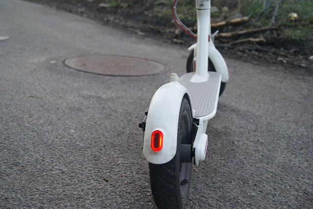 Patinete eléctrico blanco, visto desde detrás. Situado en una calle.